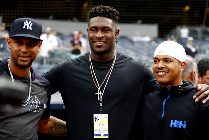 Seattle Seahawks draft pick Dekaylin Metcalf, center, poses for a photo with New York Yankees' Aaron Hicks, left, and Toronto Blue Jays starting pitcher Marcus Stroman before a baseball game between the Yankees and the Blue Jays, Monday, June 24, 2019, in New York. (AP Photo/Kathy Willens)