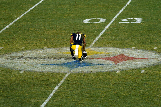Pittsburgh Steelers wide receiver Chase Claypool (11) kneels on the team logo after the team was defeated by the Cleveland Browns in an NFL wild-card playoff football game, late Sunday, Jan. 10, 2021, in Pittsburgh. (AP Photo/Keith Srakocic)