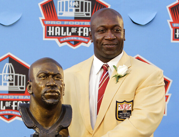 FILE -In this Aug. 7, 2010, file photo, Former Minnesota Vikings great John Randle poses with his bust after enshrinement in the Pro Football Hall of Fame in Canton, Ohio Saturday, Aug. 7, 2010. Randle did enough great things on the football field to be inducted into the Pro Football Hall of Fame. He is being rewarded after his playing career not with such accolades, but simply with being able to help others. (AP Photo/Mark Duncan, File)