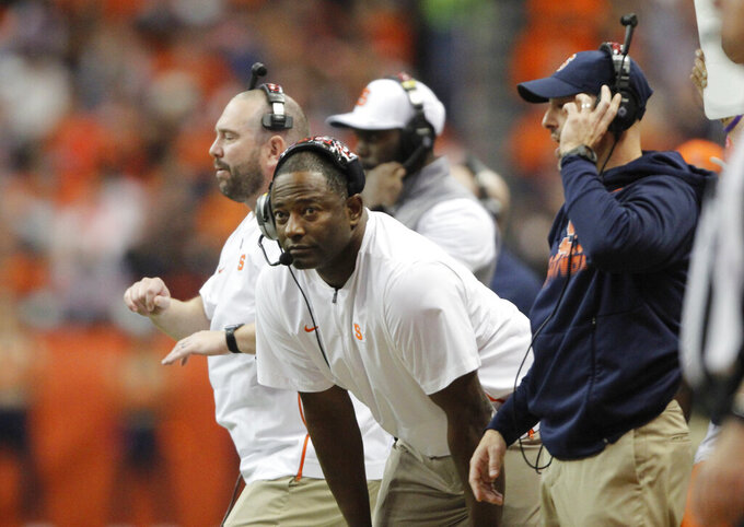 Syracuse coach Dino Babers, center, looks at the clock during the first quarter of the team's NCAA college football game against Pittsburgh in Syracuse, N.Y., Friday, Oct. 18, 2019. (AP Photo/Nick Lisi)