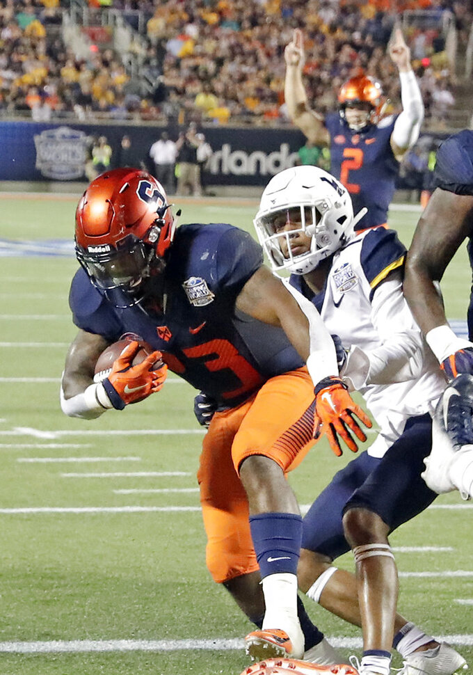 Syracuse running back Abdul Adams, left, runs for a 1-yard touchdown past West Virginia cornerback Derrek Pitts Jr. (1) during the first half of the Camping World Bowl NCAA college football game Friday, Dec. 28, 2018, in Orlando, Fla. (AP Photo/John Raoux)