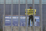 A Greenpeace activist displays a banner reading 'The climate is not a business' outside the COP25 climate talks congress in Madrid, Spain, Friday, Dec. 13, 2019. The United Nations Secretary-General has warned that failure to tackle global warming could result in economic disaster. (AP Photo/Paul White)