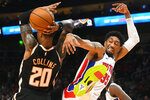 Detroit Pistons forward Christian Wood, right, comes down after blocking a shot by Atlanta Hawks forward John Collins (20) during the first half of an NBA basketball game Saturday, Jan. 18, 2020, in Atlanta. (AP Photo/John Amis)