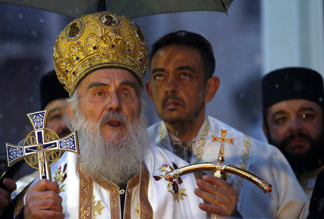 FILE - In this Jan. 6, 2019. file photo, Serbian Patriarch Irinej attends a ceremonial burning of dried oak branches, in front of church of St. Sava in Belgrade, Serbia. The Serbian Orthodox Church says Patriarch Irinej has been hospitalized after testing positive for the new coronavirus. Patriarch Irinej last Sunday led the prayers at the big public funeral for the church head in Montenegro, Bishop Amfilohije, who had died after contracting the virus. (AP Photo/Darko Vojinovic, File)