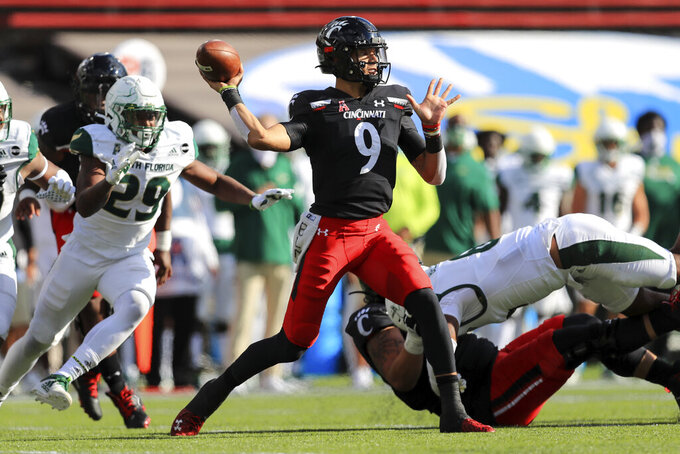 Cincinnati Desmond Ridder throws a pass during the first half of an NCAA college football game against South Florida, Saturday, Oct. 3, 2020, in Cincinnati. (AP Photo/Aaron Doster)