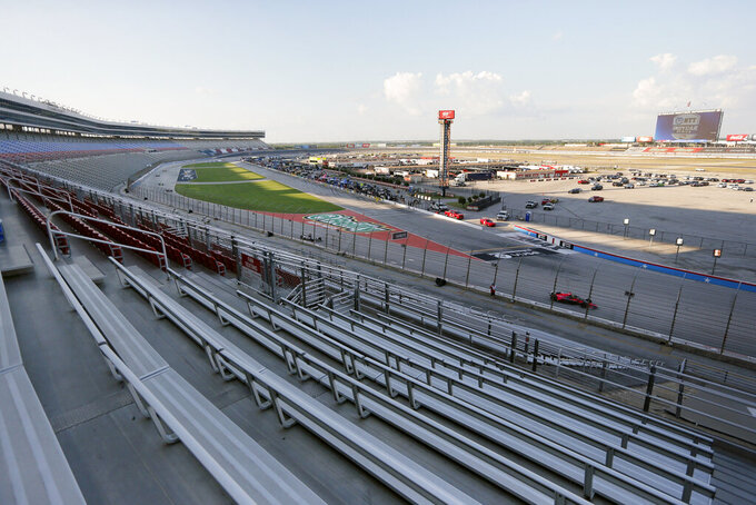An empty grandstand, foreground, is viewed as drivers head through the front stretch and into Turn 1 during an IndyCar auto race at Texas Motor Speedway in Fort Worth, Texas, Saturday, June 6, 2020. (AP Photo/Tony Gutierrez)