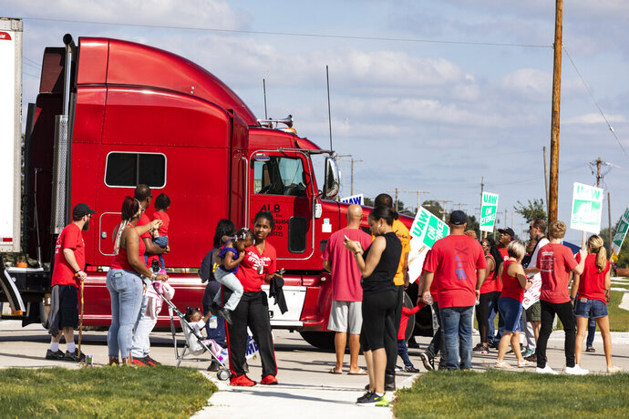Picketing union members stand-off with a semi-truck attempting to enter the GM Davison Road Processing Center. United Automobile Workers remain on strike against GM on Tuesday, Sept. 17, 2019 in Burton, Mich. (Sara Faraj/The Flint Journal via AP)