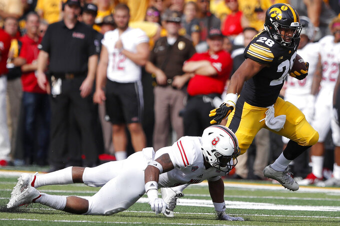 Iowa running back Toren Young (28) runs from Northern Illinois safety Mykelti Williams during the second half of an NCAA college football game, Saturday, Sept. 1, 2018, in Iowa City, Iowa. Iowa won 33-7. (AP Photo/Charlie Neibergall)
