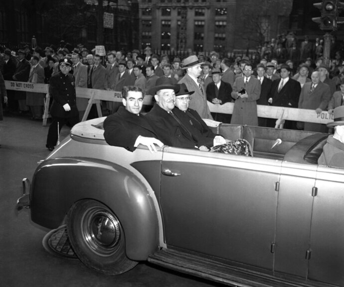 "FILE - In this Nov. 21, 1949, file photo, Shah Mohammad Reza Pahlavi of Iran, left, Grover Whalen, representing the Mayor of New York, center, and Hussein Ala, Iranian Ambassador to the U.S., right, ride through Broadway on their way to an official reception for Pahlavi at City Hall, in New York. It wasn't always the case of venturing into ""enemy"" territory for Iranian leaders when they visited the United Nations in New York. Shah Mohammad Reza Pahlavi was a key U.S. ally for decades. (AP Photo/File)"