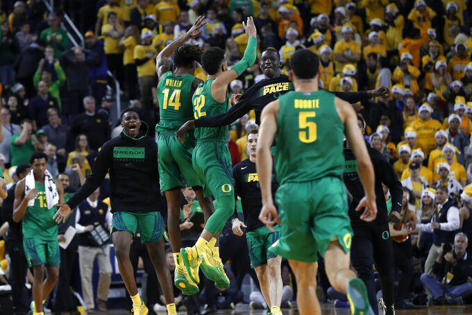 Oregon players celebrate their 71-70 overtime win against Michigan after an NCAA college basketball game in Ann Arbor, Mich., Saturday, Dec. 14, 2019. (AP Photo/Paul Sancya)