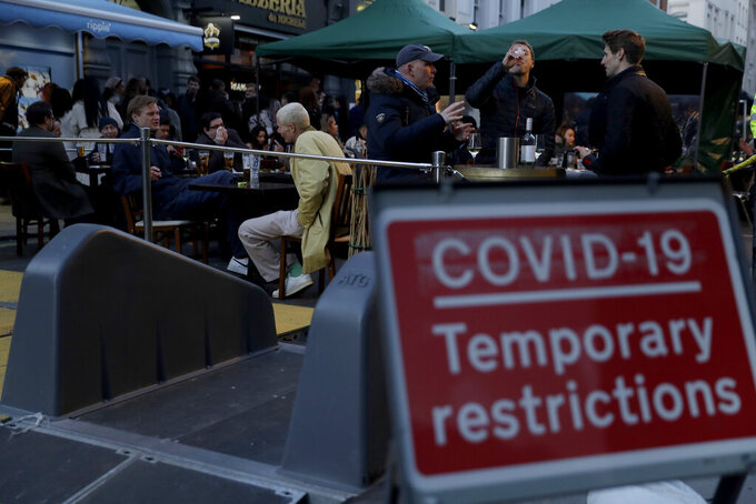 """People sit at outdoor tables setup today for drinks to be served in the Soho area of central London, on the day some of England's third coronavirus lockdown restrictions were eased by the British government, Monday, April 12, 2021. People across England can get their hair cut, eat and drink outside at restaurants and browse for clothes, books and other """"non-essential"""" items as shops and gyms reopened Monday after months of lockdown. (AP Photo/Matt Dunham)"""