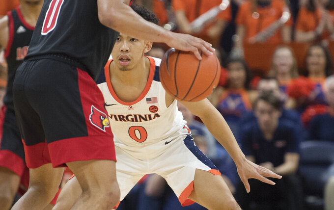 Virginia guard Kihei Clark (0) stays close to Louisville guard Lamar Kimble (0) during the second half of an NCAA college basketball game in Charlottesville, Va., Saturday, March 7, 2020. (AP Photo/Lee Luther Jr.)