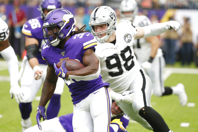 Minnesota Vikings running back Dalvin Cook (33) runs from Oakland Raiders defensive end Maxx Crosby (98) during the first half of an NFL football game, Sunday, Sept. 22, 2019, in Minneapolis. (AP Photo/Bruce Kluckhohn)