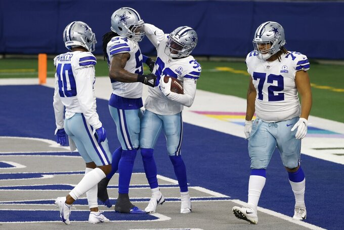 Dallas Cowboys' Steven Parker (40), Jaylon Smith, second from left, Anthony Brown (30) and Trysten Hill (72) celebrate a touchdown scored by Brown after he recovered a New York Giants fumble in the first half of an NFL football game in Arlington, Texas, Sunday, Oct. 11, 2020. (AP Photo/Ron Jenkins)