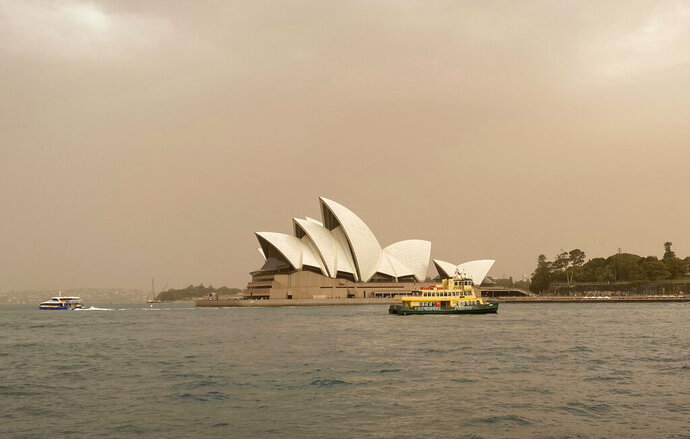 Sydney Opera House is backdropped by haze from wildfires near the city, in Sydney, Australia, Tuesday Nov. 12, 2019.   Authorities have declared a state of emergency as ferocious wildfires are burning across Australia's most populous state and into the suburbs of Sydney on Tuesday, with winds carrying embers for kilometers (miles) and igniting new fire spots. (Mette Estep / NTB scanpix via AP)