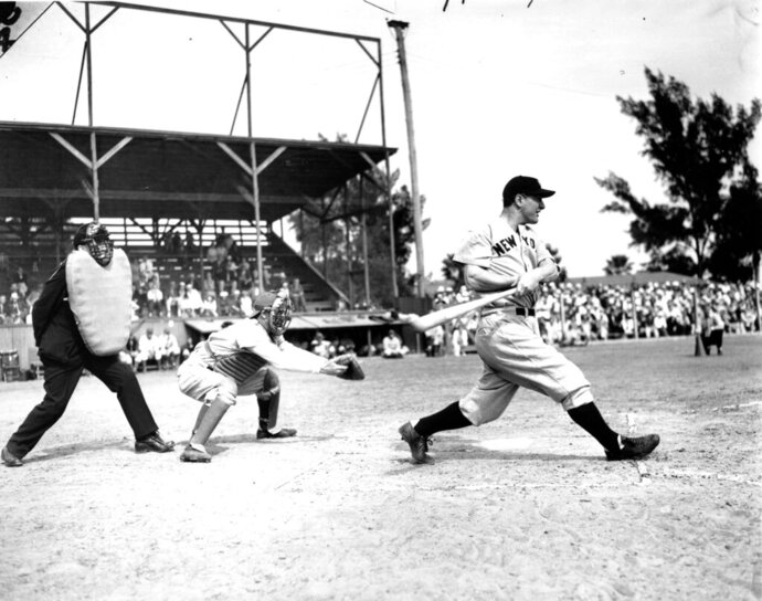 FILE- In this March 22, 1937, file photo Lou Gehrig bats the ball for the New York Yankees in his first exhibition game of the season against the Boston Bees in St. Petersburg, Fla. Al Lopez is the Bees' catcher and Tiny Parker is the home plate umpire. A collection of Gehrig memorabilia, which includes various photographs, letters and signed documents, and baseballs, is now available as part of Heritage Auctions' latest offering. (AP Photo, File)