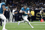 Jacksonville Jaguars quarterback Trevor Lawrence (16) scrambles in the first half of an NFL preseason football game against the New Orleans Saints in New Orleans, Monday, Aug. 23, 2021. (AP Photo/Derick Hingle)