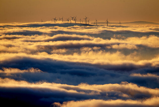 Wind turbines stand on a hill and are surrounded by fog and clouds in the Taunus region near Frankfurt, Germany, Monday, Jan. 6, 2020. (AP Photo/Michael Probst)