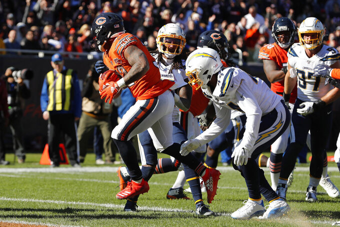 Chicago Bears running back David Montgomery, left, scores on a 4-yard touchdown run ahead of Los Angeles Chargers outside linebacker Kyzir White, right, during the second half of an NFL football game, Sunday, Oct. 27, 2019, in Chicago. (AP Photo/Charles Rex Arbogast)