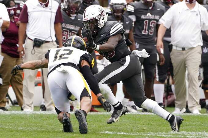 Alabama A&M running back Gary Quarles (23) fights off a tackle attempt by Arkansas-Pine Bluff defensive back Shawn Steele (12) during the second half of the Southwestern Athletic Conference championship NCAA college football game Saturday, May 1, 2021, in Jackson, Miss. Alabama A&M won 40-33. (AP Photo/Rogelio V. Solis)