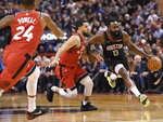 Houston Rockets guard James Harden (13) drives past Toronto Raptors guard Fred VanVleet (23) as Raptors guard Norman Powell (24) moves in during second half NBA action in Toronto on Thursday, Dec.5, 2019. (Nathan Denette/The Canadian Press via AP)