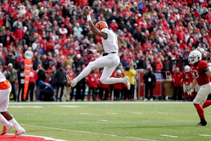 Illinois quarterback AJBush Jr. (1) leaps into the end zone for a touchdown ahead of Nebraska defensive back JoJo Domann (13), during the first half of an NCAA college football game in Lincoln, Neb., Saturday, Nov. 10, 2018. (AP Photo/Nati Harnik)