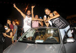 Demonstrators celebrate from the car during a rally after the president suspended the legislature and fired the prime minister in Tunis, Tunisia, Sunday, July 25, 2021. Protesters celebrated President Kais Saied's decision late Sunday night with shouts of joy, honking of horns and waving Tunisian flags. (AP Photo/Hedi Azouz)