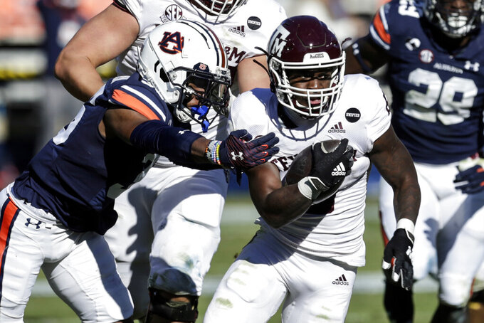 Texas A&M running back Devon Achane (6) carries the ball as Auburn defensive back Jaylin Simpson (36) tries to stop him during the second half of an NCAA college football game on Saturday, Dec. 5, 2020, in Auburn, Ala. (AP Photo/Butch Dill)