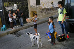 A child plays with a traffic cone in the Catia neighborhood of Caracas, Venezuela, Saturday, April 17, 2021, amid the new coronavirus pandemic. (AP Photo/Matias Delacroix)