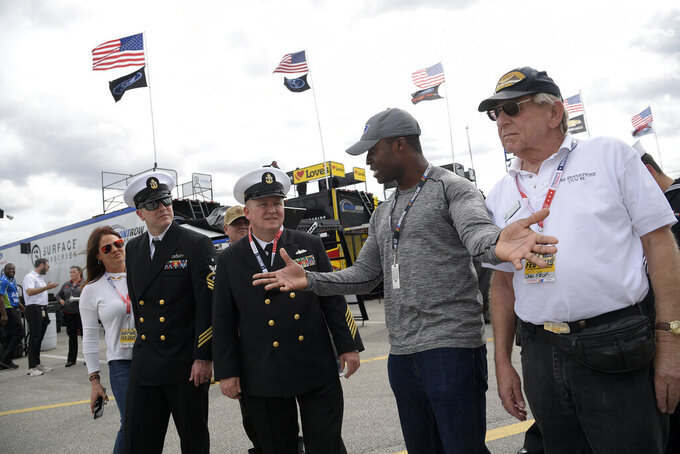 Driver Jesse Iwuji, second from right, talks to military personal, while leading a tour of the garage area, during a practice session for the NASCAR Daytona 500 auto race at Daytona International Speedway Saturday, Feb. 16, 2019, in Daytona Beach, Fla. (AP Photo/Phelan M. Ebenhack)