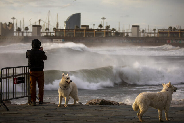 A man photographs the Mediterranean sea during strong winds in Barcelona, Spain, Monday, Jan. 20, 2020. Two people have died as storms carrying heavy snowfalls and gale-force winds lashed many parts of Spain on Monday. The storm has forced the closure of Alicante airport and some 30 roads in eastern region. Six provinces are on top alert. (AP Photo/Emilio Morenatti)