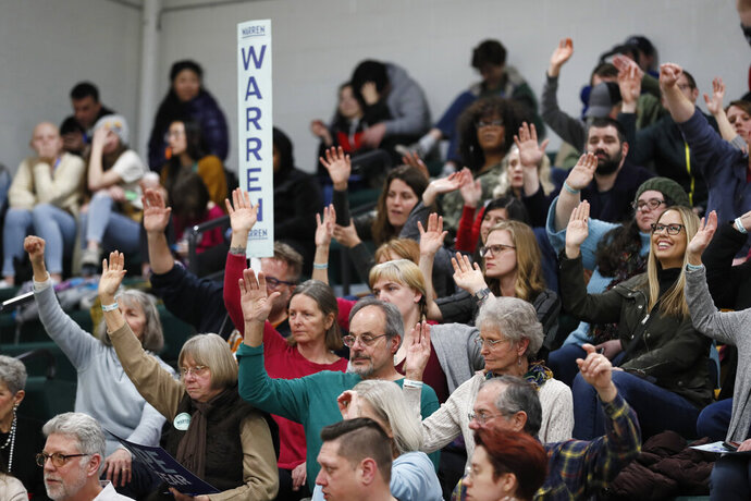 Supporters for Democratic presidential candidate Sen. Elizabeth Warren, D-Mass., raise their hands to be counted during a Democratic party caucus at Hoover High School, Monday, Feb. 3, 2020, in Des Moines, Iowa. (AP Photo/Charlie Neibergall)