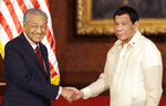 Philippine President Rodrigo Duterte, right, poses with Malaysian Prime Minister Mahathir Mohamad for a photo after their joint press statement at the Malacanang presidential palace in Manila, Philippines, Thursday, March 7, 2019. (AP Photo/Aaron Favila)