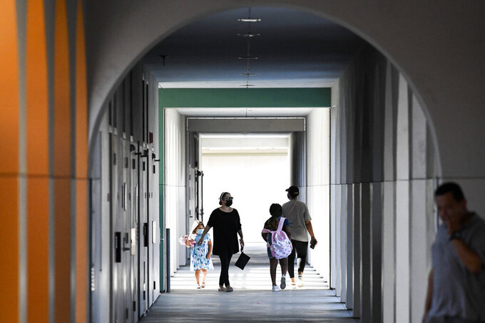 Parents walk with their children on the first day of school at Enrique S. Camarena Elementary School, Wednesday, July 21, 2021, in Chula Vista, Calif. The school is among the first in the state to start the 2021-22 school year with full-day, in-person learning. (AP Photo/Denis Poroy)