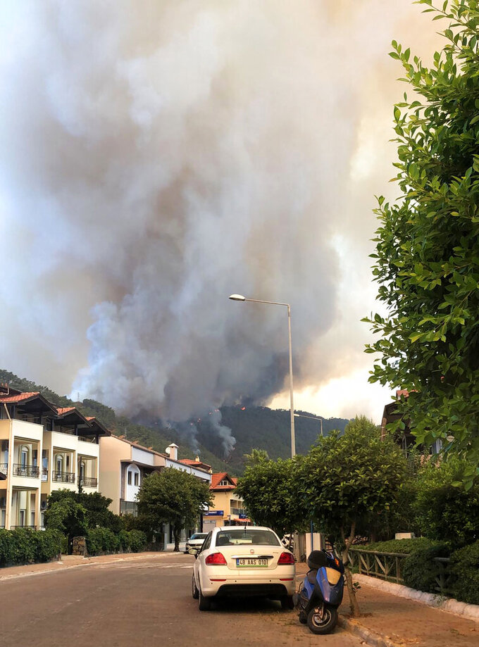 Smoke rises from a forest fire close to a touristic hotel in Icmeler area in the Aegean coastal town of Marmaris, Turkey, Thursday, July 29, 2021. At least three people were killed and dozens of people were hospitalized in Manavgat in southern Turkey after strong winds fanned several separate forest fires, officials said Thursday. (AP Photo/Patrizia Under)