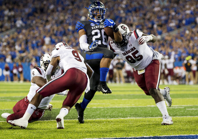 Kentucky running back Benny Snell Jr. (26) is tackled by several South Carolina defenders during the first half of an NCAA college football game in Lexington, Ky., Saturday, Sept. 29, 2018. (AP Photo/Bryan Woolston)