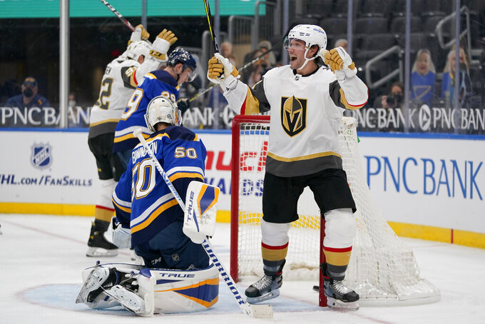 Vegas Golden Knights' Alec Martinez, right, celebrates after scoring past St. Louis Blues goaltender Jordan Binnington (50) during the third period of an NHL hockey game Friday, March 12, 2021, in St. Louis. (AP Photo/Jeff Roberson)