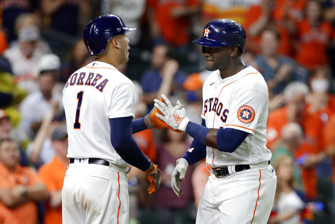 Houston Astros' Carlos Correa (1) and Yordan Alvarez, right, celebrate Alvarez's home run against the Oakland Athletics during the sixth inning of a baseball game Thursday, April 8, 2021, in Houston. (AP Photo/Michael Wyke)