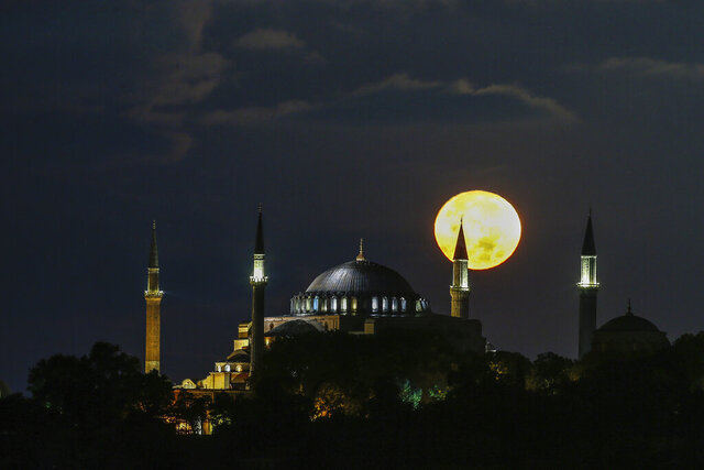 The full moon rises behind the Byzantine-era Hagia Sophia in the historic Sultanahmet district of Istanbul, early Tuesday, Sept. 1, 2020. Worshipers held the first Muslim prayers in 86 years inside the Istanbul landmark that served as one of Christendom's most significant cathedrals, a mosque and a museum before its conversion back into a Muslim place of worship on July 24, 2020. The conversion of the edifice, has led to an international outcry. (AP Photo/Emrah Gurel)