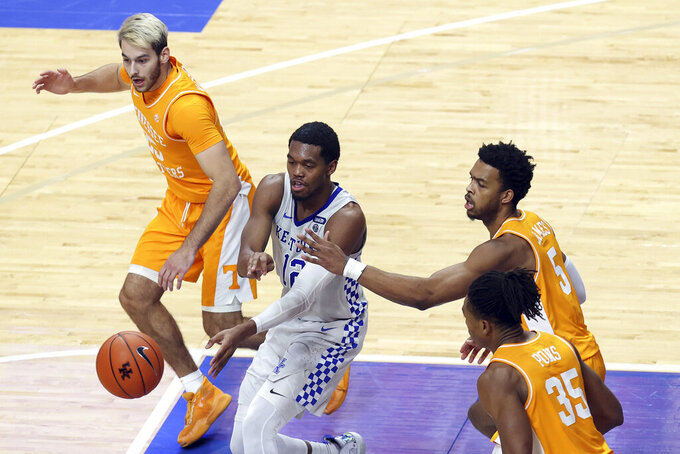 Kentucky's Keion Brooks Jr., middle, passes while defended by Tennessee's Santiago Vescovi (25), Josiah-Jordan James (5) and Yves Pons (35) during the second half of an NCAA college basketball game in Lexington, Ky., Saturday, Feb. 6, 2021. (AP Photo/James Crisp)