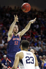 Saint Mary's Tommy Kuhse (12) shoots as BYU's Yoeli Childs (23) defends during the first half of an NCAA college basketball game in the West Coast Conference tournament, Monday, March 9, 2020, in Las Vegas. (AP Photo/Isaac Brekken)