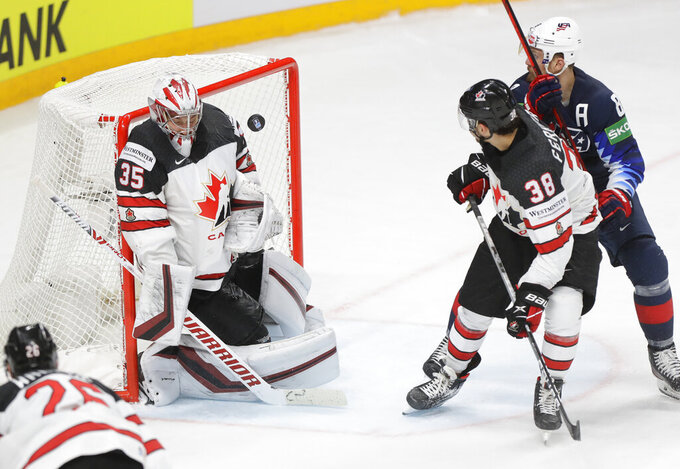 Canada's goaltender Darcy Kuemper, left, Canada's Mario Ferraro and Matt Tennyson of the US in action during the Ice Hockey World Championship semifinal match between the United States and Canada at the Arena in Riga, Latvia, Saturday, June 5, 2021. (AP Photo/Sergei Grits)