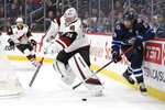 Winnipeg Jets' Blake Wheeler (26) grabs the loose puck as Arizona Coyotes goaltender Darcy Kuemper (35) goes behind the net during the second period of an NHL hockey game Tuesday, Oct. 15, 2019, in Winnipeg, Manitoba. (Fred Greenslade/The Canadian Press via AP)