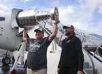 Tampa Bay Lightning owner Jeff Vinik, left, holds the Stanley Cup as team captain Steven Stamkos looks on after the NHL hockey team arrived in Tampa, Fla., Tuesday, Sept. 29, 2020. Tampa Bay clinched the Cup with a 2-0 win in Game 6 against Dallas on Monday night in Edmonton, Alberta. (Luis Santana/Tampa Bay Times via AP)