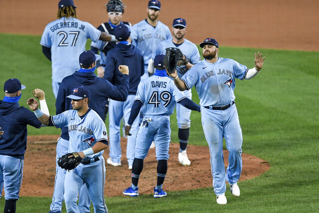 Toronto Blue Jays first baseman Rowdy Tellez, right, celebrates a win over the New York Yankees with teammates after a baseball game in Buffalo, N.Y., Monday, Sept. 7, 2020. (AP Photo/Adrian Kraus)
