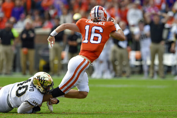 Clemson's Trevor Lawrence is sacked by Wake Forest's Rondell Bothroyd during the first half of an NCAA college football game Saturday, Nov. 16, 2019, in Clemson, S.C. (AP Photo/Richard Shiro)