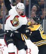 Boston Bruins' Sean Kuraly (52) checks Ottawa Senators' Thomas Chabot (72) during the third period of an NHL hockey game in Boston, Saturday, March 9, 2019. (AP Photo/Michael Dwyer)