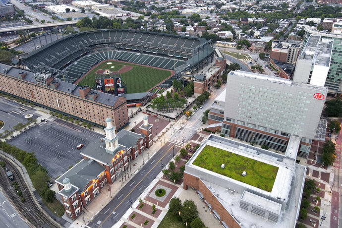 In a photo taken Saturday, June 27, 2020, a Hilton hotel, top right, is seen adjacent to the Oriole Park at Camden Yards stadium in Baltimore. With the baseball season starting amidst coronavirus restrictions limiting fans from attending games, tall structures such as the Hilton hotel will offer a bird's eye view of games. (AP Photo/Julio Cortez)