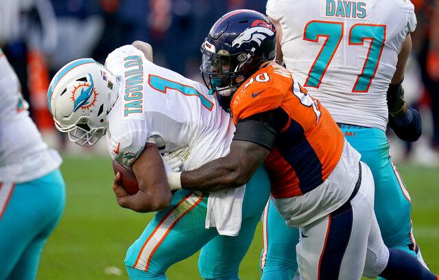 Denver Broncos defensive end DeShawn Williams (90) sacks Miami Dolphins quarterback Tua Tagovailoa (1) during the second half of an NFL football game, Sunday, Nov. 22, 2020, in Denver. (AP Photo/David Zalubowski)
