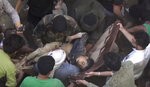 EDS NOTE: GRAPHIC CONTENT -- In this frame grab from from video, people carry a child's body after pulling it out from rubble following Saudi-led coalition airstrikes that killed at least six, including four children, officials said, in the residential center of the capital, Sanaa, Yemen. The Sanaa airstrikes came after Yemen's Iran-backed Houthi rebels, who control the capital, launched a drone attack earlier in the week on a critical oil pipeline in Saudi Arabia, Tehran's biggest rival in the region. (AP Photo)